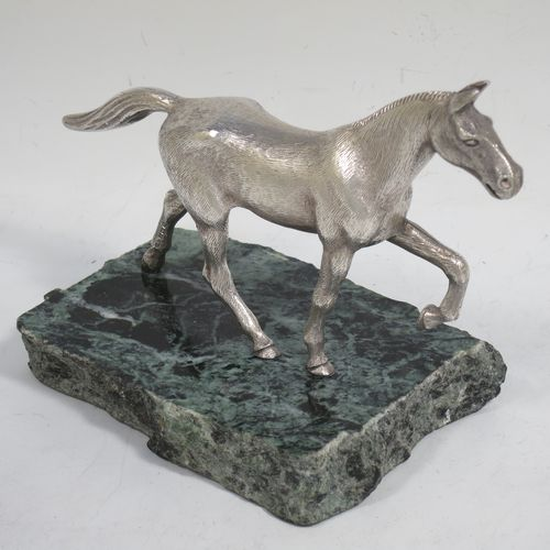 A handsome Sterling Silver cast model of a horse in a cantering pose, and fixed to a green marble base. Made by Albert Edward Jones of Birmingham in 1972. The dimensions of this fine hand-made silver horse are height 11.5 cms (4.5 inches), and length 15 cms (6 inches).
