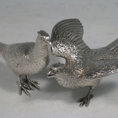 Sterling silver pair of cast pheasants, showing two male cock birds, with realistically hand-chased feathers. Made by A.E. Jones of Birmingham in 1975. The dimensions of these sterling silver pheasants are: length of startled bird out 16.5 cms (6.5 inches), height of resting bird 8 cms (3 inches), width of startled bird 10 cms (4 inches). Weight approx. 483g (15.6 troy ounces).