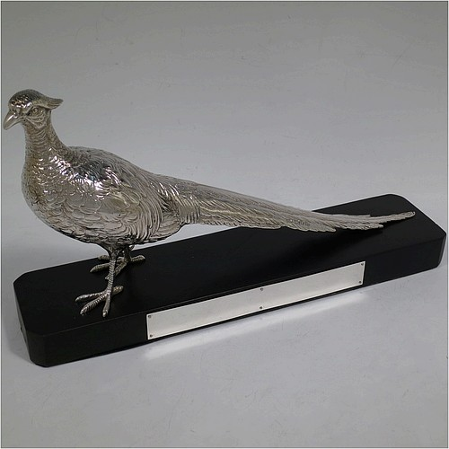 A very handsome cast Sterling Silver single pheasant model, showing a male bird in a realistic traditional pose, finely detailed with hand-chased body and tail feathers, and all sitting on a black presentation plinth with silver plaque. Made by Jones and Son of London in 1935. The dimensions of this fine hand-made sterling silver pheasant are length 30.5 cms (12 inches), height 13.5 cms (5.3 inches), and it weighs approx. 465g (15 troy ounces).