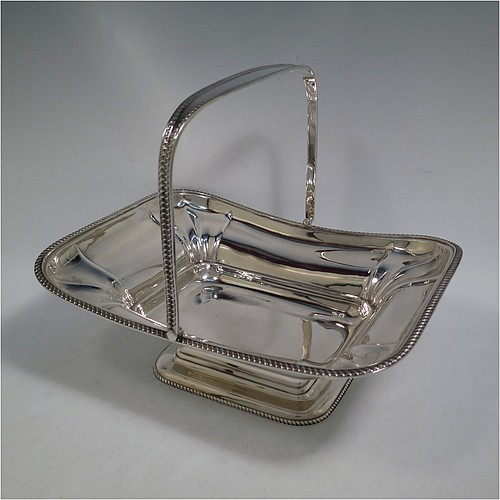 An Antique Edwardian Sterling Silver basket, having a rectangular body, with an applied gadroon border, a hinged and swing handle with gadroon edges, all sitting on a pedestal foot. Made by the Dixon Brothers of Sheffield in 1910. The dimensions of this fine hand-made antique silver basket are height 23 cms (9 inches), length 27.5 cms (10.75 inches), width 21 cms (8.25 inches), and it weighs approx. 746g (24 troy ounces).
