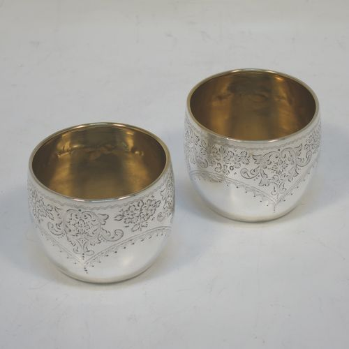 A small but very pretty pair of Antique Victorian Sterling Silver cups, having round bodies with hand-engraved floral and scroll decoration, gold-gilt interiors, and all sitting on flat bases. Made in London in 1886. The dimensions of these fine hand-made antique silver cups are height 4 cms (1.5 inches), diameter 4.5 cms (1.75 inches), and their total weight is approx. 57g (1.8 troy ounces).