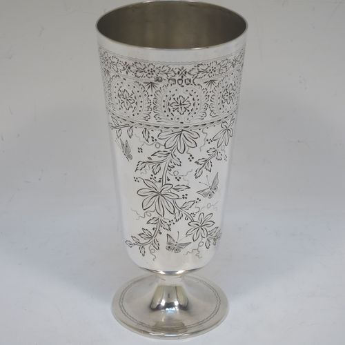 A very pretty Antique Victorian Sterling Silver beaker, having a round straight-sided body with tapering sides, with hand-engraved floral decoration and butterflies, and vacant cartouches either side, and all sitting on a round pedestal foot. Made by Charles Boyton of London in 1885. The dimensions of this fine hand-made antique silver beaker are height 14 cms (5.5 inches), diameter at top 6.5 cms (2.5 inches), and it weighs approx. 171g (5.5 troy ounces).