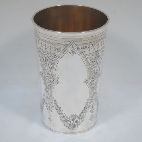 A very pretty and large Antique Victorian Sterling Silver beaker, having a round straight-sided body with tapering sides, with hand-engraved scroll and floral decoration  surrounding four vacant cartouches, a gold-gilt interior, and all sitting on a flat base. Made by William Evans of London in 1875. The dimensions of this fine hand-made antique silver beaker are height 12.5 cms (5 inches), diameter at top 8 cms (3 inches), and it weighs approx. 170g (5.5 troy ounces).