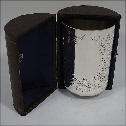 An Antique Victorian Sterling Silver beaker, having a round straight-sided body with tucked under flat base, with hand-engraved fern-work, two vacant oval cartouches on either side, with a gold-gilt interior, and in its original dark blue satin and velvet-lined presentation box. Made by Wakely and Wheeler of London in 1887. The dimensions of this fine hand-made antique silver beaker are height 10 cms (4 inches), diameter at top 7 cms (2.75 inches), and it weighs approx. 129g (4.2 troy ounces). Please note that the box is embossed with initials on the exterior.