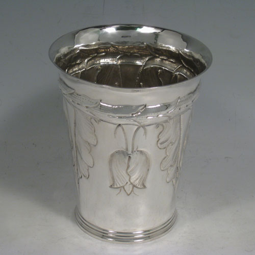 A very unusual and pretty Britannia Standard Silver Art Nouveau style beaker, having a round body with tapering sides, hand-chased floral decoration with tulips, and sitting on a collet foot. Made by S. J. Phillips of London in 1935, with extra Jubilee mark. The dimensions of this fine hand-made silver beaker are height 12 cms (4.75 inches), diameter at top 10 cms (4 inches), and it weighs approx. 244g (7.9 troy ounces).