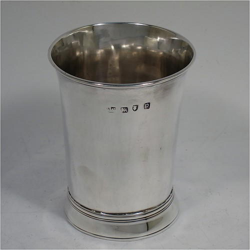 A very handsome Antique Georgian Sterling Silver beaker, having a very plain round body with tapering sides, reeded top and bottom borders, and sitting on a collet foot. Made by Thomas Wallis I  of London in 1770. The dimensions of this fine hand-made antique silver beaker are height 9 cms (3.5 inches), diameter at top 7 cms (2.75 inches), and it weighs approx. 123g (4 troy ounces).