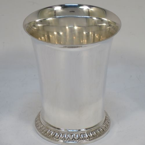 A very handsome Sterling Silver beaker cup, having a plain round body with tapering sides, and sitting on a collet foot with a leaf and bead border. Made by Goldsmiths and Silversmiths of London in 1939. The dimensions of this fine hand-made silver beaker cup are height 8.5 cms (3.3 inches), diameter at top 7 cms (2.75 inches), and it weighs approx. 95g (3 troy ounces).