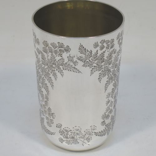 A very pretty Antique Victorian Sterling Silver beaker, having a round straight-sided body with tapering sides and a tucked under base, with hand-engraved ferns and gingko leaves surrounding two vacant cartouches either side, a gold-gilt interior and all sitting on a flat base. Made by F. C. W. Ltd., of London in 1889. The dimensions of this fine hand-made antique silver beaker are height 9 cms (3.5 inches), diameter at top 6 cms (2.25 inches), and it weighs approx. 75g (2.4 troy ounces).