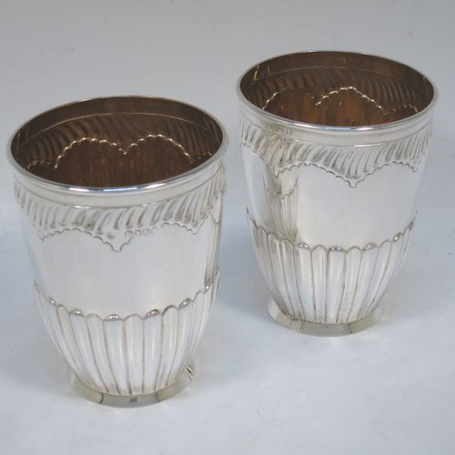 A very pretty Antique Victorian Sterling Silver pair of beaker cups, having round bodies with tapering sides and hand-chased fluted decoration, god-gilt interiors, and sitting on a collet feet. Made by H. J. Lias and J. Wakely of London in 1882. The dimensions of this fine pair of hand-made antique silver beakers are height 10.5 cms (4.25 inches), diameter at top 8 cms (3.25 inches), and they weigh a total of approx. 282g (9 troy ounces).