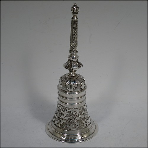 A very handsome, large and heavy sterling silver table bell having a round baluster body with hand-chased acanthus-leaf, scroll and floral decoration, a cast floral and scroll handle, and an original silver clapper. Made in London in 1967. The dimensions of this fine hand-made silver table bell are height 18 cms (7 inches), diameter at base 7 cms (2.75 inches), and it weighs approx. 361g (11.6 troy ounces).