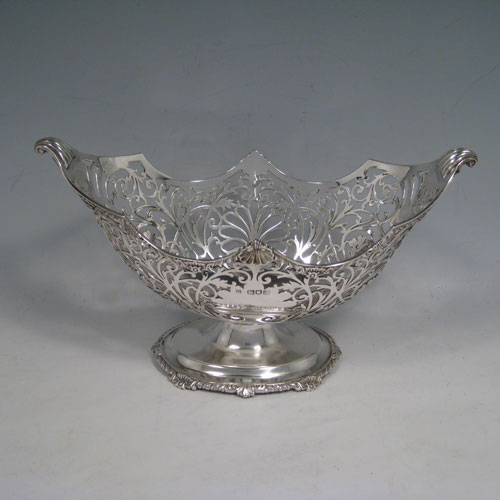Antique Edwardian sterling silver bon-bon dish, having an oval hand-pierced body, applied shell and gadroon borders, cast shell and fluted handles, and sitting on a pedestal foot. Made by Jackson and Fullerton of London in 1904. Height 14 cms (5.5 inches), length 24 cms (9.5 inches), width 13 cms (5 inches). Weight approx. 383g (12.4 troy ounces).