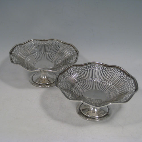 Antique Edwardian sterling silver pair of bon-bon dishes, having round hand-pierced bodies, with applied wave-edged reeded borders, and sitting on plain round pedestal feet. Made by Walker and Hall of Sheffield in 1910. The dimensions of these fine hand-made silver bon-bon dishes are height 6 cms (2.3 inches), diameter 12.5 cms (5 inches), and the weigh a total of approx. 190g (6 troy ounces).