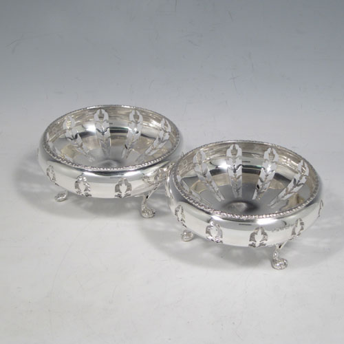 Antique Sterling silver pair of very pretty bon-bon dishes, having round bodies with hand-pierced floral decoration, applied floral borders, and sitting on three pierced claw feet. Made by Elkington and Co., of Birmingham in 1911. The dimensions of this fine pair of hand-made silver bon-bon dishes are diameter 10 cms (4 inches), height 5 cms (2 inches), and they weigh a total of 165g (5.3 troy ounces).