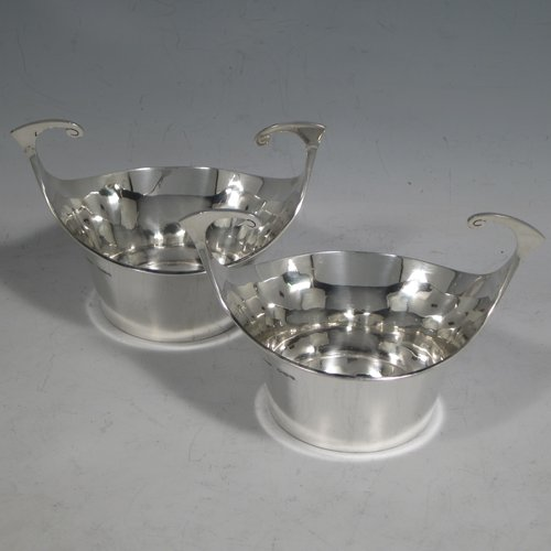 Antique Edwardian sterling silver pair of bon-bon dishes, having plain round bodies, with very unusual flying scroll handles, and each sitting on flat bases. Originally imported into, and hallmarked for, London in 1905. The dimensions of this fine pair of hand-made silver bon-bon dishes are width across handles 12 cms (4.75 inches), height 8 cms (3.25 inches), and they weigh a total of 180g (5.3 troy ounces).