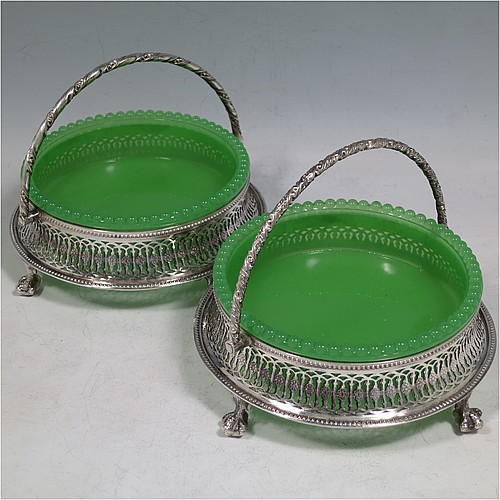 An Antique Victorian Silver Plated pair of bon-bon dishes, having round bodies with original green jelly glass liners, with hand-pierced geometrical and floral decoration, applied bead-edged borders and hinged rope-twist swing handles, all sitting on four cast claw & ball feet. Made in ca. 1880. The dimensions of this fine pair of hand-made antique silver-plated bon-bon dishes are diameter 14 cms (5.5 inches), and height (inc. handle) 12 cms (4.75 inches).