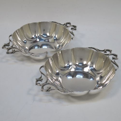A very pretty Antique Edwardian Sterling Silver pair of bon-bon dishes, having rounded bodies with hand-chased lobed decoration, with beautiful scroll work side-handles, and all sitting on flat bases. Made by Roberts and Belk of Sheffield in 1908. The dimensions of this fine hand-made pair of antique silver bon-bon dishes  are length (inc. handles) 16 cms (6.25 inches), diameter 12 cms (4.75 inches), height 3.5 cms (1.3 inches), and they weigh a total of approx. 310g (10 troy ounces).