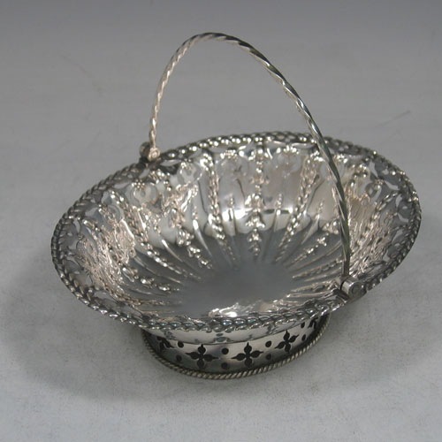Antique Georgian sterling silver sweet-meat basket, having hand-pierced and chased decoration, a rope-twist swing handle, and sitting on a collet foot with applied rope-twist edge. Made in London in 1774. Length 15 cms (6 inches), width 12 cms (4.75 inches). Weight approx. 108g (3.5 troy ounces)