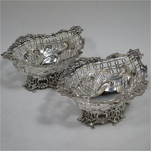 A very pretty Antique Victorian Sterling Silver pair of bon-bon baskets or dishes, having oval bodies with hand-pierced geometrical and scroll work decoration, an applied cast floral and scroll border, and sitting on matching pierced feet. Made by William Comyns of London in 1892. The dimensions of this fine hand-made pair of antique silver bon-bon dishes or baskets are length 16 cms (6.25 inches), width 12 cms (4.75 inches), height 7 cms (2.75 inches), and they weigh a total of  approx. 328g (10.6 troy ounces).
