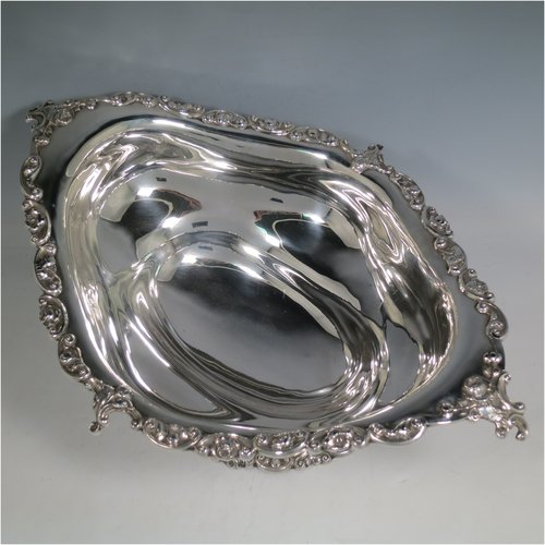 An Antique Edwardian Sterling Silver large and heavy table bowl, having an oval plain baluster body, with applied cast floral borders, and sitting on a pedestal foot. Made by Charles Clement Pilling of  Sheffield in 1909. The dimensions of this fine hand-made antique silver table bowl are length 41 cms (16 inches), width 28 cms (11 inches), height 16 cms (6.25 inches), and it weighs approx. 1,287g (41 troy ounces).