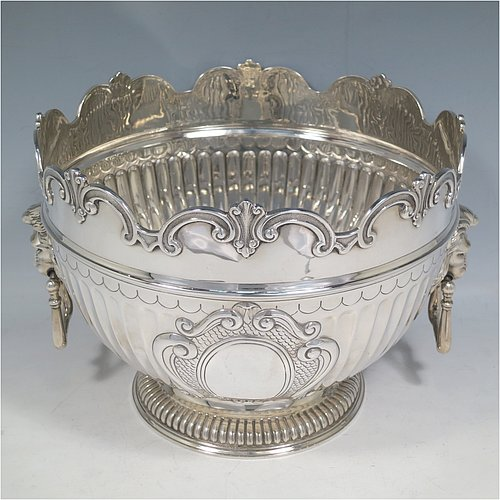 An Antique Edwardian Sterling Silver Montieth style bowl, having a round body with an applied scroll border, with hand-chased half-fluted decoration, together with two cast lion-mask side-handles, and sitting on a pedestal foot. Made by Elkington & Co.,of London in 1910. The dimensions of this fine hand-made antique silver table bowl are diameter 22 cms (8.75 inches), height 16.5 cms (6.5 inches), and it weighs approx. 930g (30 troy ounces).