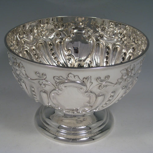 Antique Edwardian sterling silver hand-chased rose bowl, with floral and swirl-fluted decoration, sitting on a pedestal foot. Made by Nathan and Hayes of Birmingham in 1905. Height 14.5 cms (5.75 inches), diameter 21 cms (8.25 inches). Weight approx. 630g (20.3 troy ounces).