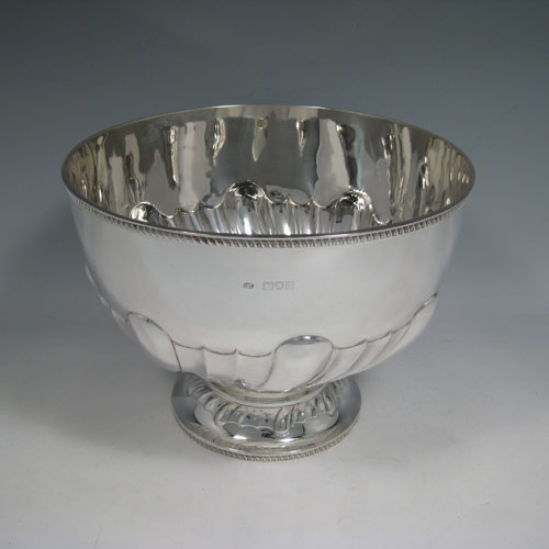 Antique Edwardian sterling silver bowl, having a round hand-chased body with large swirl-fluting, a matching pedestal foot, and applied gadroon borders. Made by Charles Boyton of London in 1903. The dimenions of this fine silver bowl are height 17 cms (6.75 inches), diameter 23 cms (9 inches), and it weighs approx. 770g (24.8 troy ounces).