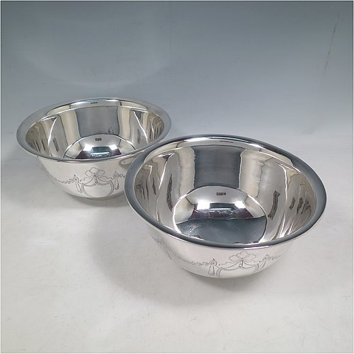 A Sterling Silver pair of Paul Revere style bowls, having plain round bodies with hand-engraved neoclassical style engraving, and sitting on collet feet. Made by Aspreys of London in 1925. The dimensions of these fine hand-made silver bowls are height 10 cms (4 inches), diameter 20 cms (8 inches), and they weigh a total of approx. 1,210g (39 troy ounces).
