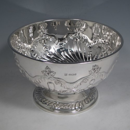 Antique Victorian sterling silver rose bowl, having a round hand-chased body with swirl fluted and floral decoration, and sitting on a pedestal foot. Made by the Deakin Brothers of Sheffield in 1897. The dimensions of this fine hand-made silver bowl are height 12 cms (4.75 inches), diameter 19.5 cms (7.75 inches), and it weighs approx. 391g (12.6 troy ounces).