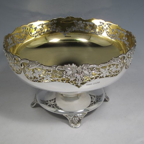 A Sterling silver table bowl, having a round body, with an applied and hand-pierced grape & vine-leaf border, with a gold-gilt interior, all sitting on a hand-pierced pedestal base with four hand-chased feet. Made by Olivant & Botsford of Sheffield in 1937. The dimensions of this fine hand-made silver bowl are diameter 21.5 cms (8.5 inches), height 14 cms (5.5 inches), and it weighs approx. 737g (23.8 troy ounces).