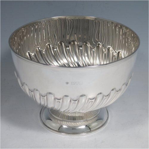 An Antique Victorian Sterling Silver Rose bowl, having a round hand-chased body with swirl half-fluted decoration, an applied reeded border, and sitting on a pedestal foot. Made by William Hutton & Sons of London in 1898. The dimensions of this fine hand-made silver bowl are height 11.5 cms (4.5 inches), diameter 16 cms (6.25 inches), and it weighs approx. 310g (10 troy ounces).