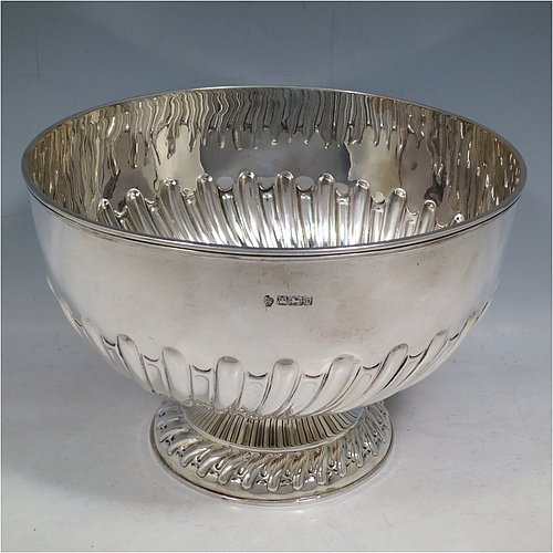 An Antique Edwardian Sterling Silver large table bowl, having a round body with an applied reeded border and hand-chased half swirl-fluted decoration, all sitting on a pedestal foot which is also fluted. Made by William Hutton of Sheffield in 1905. The dimensions of this fine hand-made antique silver table rose bowl are diameter 23.5 cms (9.25 inches), height 16 cms (6.3 inches), and it weighs approx. 616g (19.9 troy ounces).