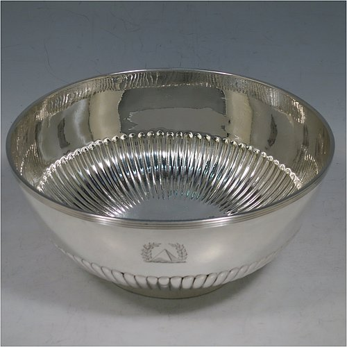 A rare Antique Georgian Sterling Silver Rose bowl, having a round body with hand-chased half-fluted decoration, an applied reeded border, and sitting on a collet foot. Made by John Robins of London in 1801. The dimensions of this fine hand-made silver bowl are height 8 cms (3.25 inches), diameter 18 cms (7 inches), and it weighs approx. 452g (14.6 troy ounces). Please note that this item is crested.