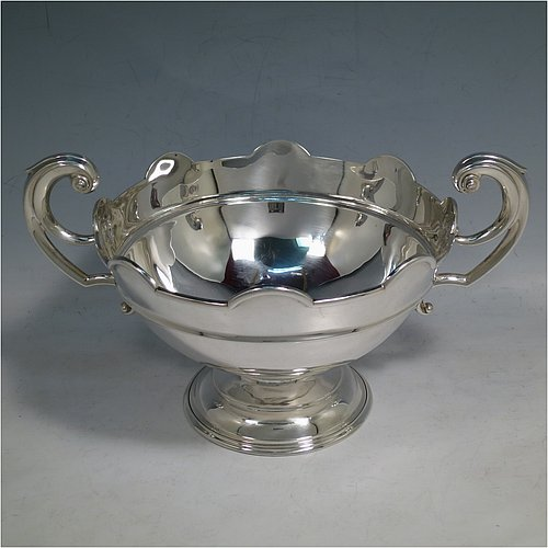 An Antique Edwardian Sterling Silver Rose bowl, having a round plain body with an applied and shaped reeded border, and a central applied band, with two flying scroll side handles, and sitting on a pedestal foot. Made by Goldsmiths & Silversmiths of London in 1910. The dimensions of this fine hand-made antique silver bowl are height (inc. handles) 14 cms (5.5 inches), diameter 17 cms (6.75 inches), and it weighs approx. 283g (9 troy ounces).