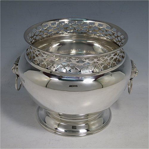 An Antique Victorian Sterling Silver table bowl, having a plain round bellied body with a hand-pierced top gallery border, together with two cast lion-mask and ring side-handles, and sitting on a plain round pedestal foot. Made by Gibson & Langland of London in 1899. The dimensions of this fine hand-made antique silver table bowl are diameter 18 cms (7 inches), height 14 cms (5.5 inches), and it weighs approx. 581g (18.7 troy ounces).