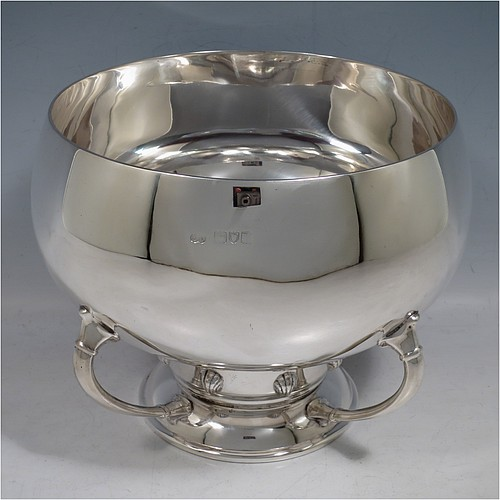 An Antique Edwardian heavy Sterling Silver Art Nouveau style table bowl, having a plain round  bellied body, sitting on a pedestal foot with four cast supports and eight applied shells. Made by the David Munsey of London in 1910. The dimensions of this fine hand-made antique silver bowl are height 16 cms (6.3 inches), diameter at top of bowl 18 cms (7 inches), and it weighs approx. 32.5 troy ounces (1,006g).