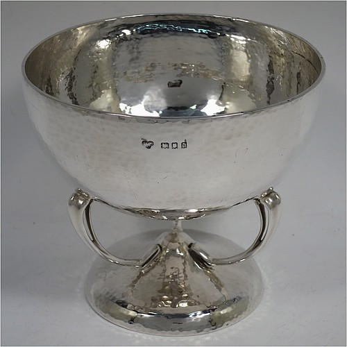A very pretty Sterling Silver Art Nouveau style table bowl, having a round hand-hammered and bellied body, with three cast scroll and tendril supports attached to a pedestal foot. Made by Goldsmiths and Silversmiths of London in 1919. The dimensions of this fine hand-made Art Nouveau hand-hammered silver bowl are height 13 cms (5 inches), diameter at top of bowl 14.5 cms (5.75 inches), and it weighs approx. 360g (11.6 troy ounces).