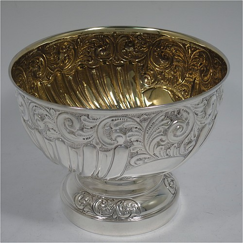 A very pretty Antique Edwardian Sterling Silver bowl, having a round body with hand-chased floral, scroll, and fluted decoration, an applied reeded border and a gold gilt interior, and all sitting on a pedestal foot with matching decoration. Made by William Hutton of Birmingham in 1906. The dimensions of this fine hand-made antique silver bowl are diameter 15 cms (6 inches), height 12 cms (4.75 inches), and it weighs approx. 247g (8 troy ounces).