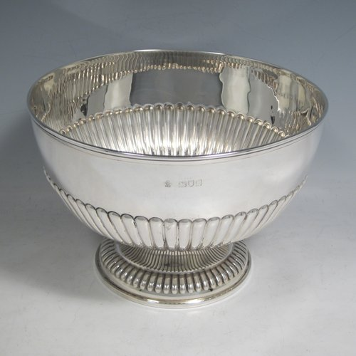 Antique Victorian sterling silver bowl, having a round hand-chased body with half-fluted decoration, an applied reeded border, and sitting on a matching pedestal foot. Made by William Hutton and Sons of London in 1898. The dimenions of this fine hand-made silver bowl are height 14 cms (5.5 inches), diameter 21 cms (8.25 inches), and it weighs approx. 525g (17 troy ounces).