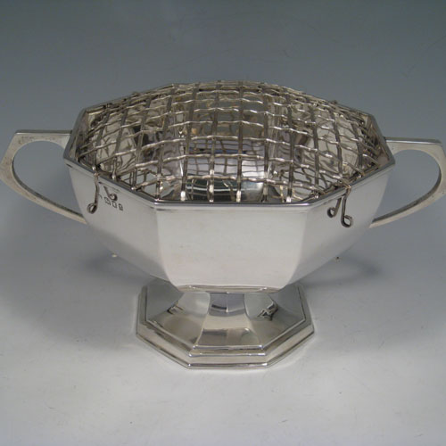 Sterling silver two-handled rose bowl, having a plain octagonal panelled body, two scroll handles, and sitting on a pedestal foot. Made by Kemp Brothers of London in 1922. Height 12.5 cms (5 inches), spread across handles 28 cms (11 inches). Weight approx. 750g (24 troy ounces). Please note that this bowl does NOT come with a rose grill.
