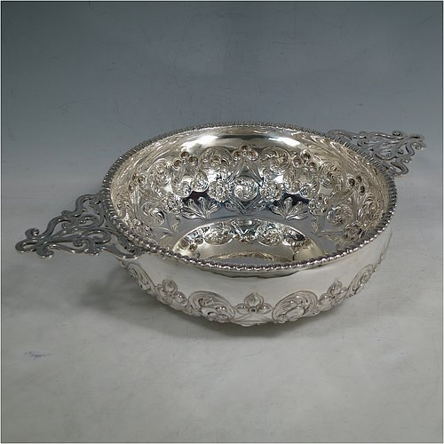 An Antique Edwardian Sterling Silver quaich style rose bowl, having a round bellied body with hand-chased floral decoration. an applied straight gadroon border, with two hand-pierced side-handles, and sitting on a flat base. Made by Peter Henderson Deere of London in 1909. The dimensions of this fine hand-made antique silver rose bowl in a quaich form are height 7 cms (2.75 inches), diameter 21.5 cms (8.5 inches), and it weighs approx. 669g (21.6 troy ounces).