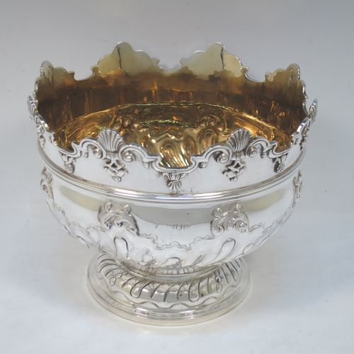 A very pretty Antique Victorian Sterling Silver Montieth style rose bowl, having a round body with hand-chased swirl half-fluting and a gold-gilt interior, below an applied reeded band, an applied shell and scroll border, and all sitting on a pedestal foot. Made by Charles Stuart Harris of London in 1900. The dimensions of this fine hand-made antique silver rose Montieth bowl are height 15 cms (6 inches), diameter 19 cms (7.5 inches), and it weighs approx. 740g (23.9 troy ounces).