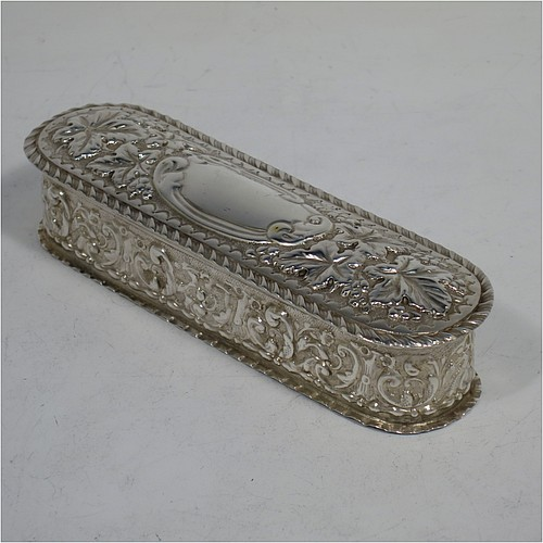 A very pretty Antique Edwardian Sterling silver table box, having a rectangular body with rounded ends and applied gadroon borders, with hand-chased grape-vine and scroll decoration, a hinged lid with central vacant cartouche, a gold-gilt interior and sitting on a flat base. Made by William Aitken of Birmingham in 1902. The dimensions of this fine hand-made antique silver box are length 13 cms (5 inches), width 4 cms (1.5 inches), height 3 cms (1.25 inches), and it weighs approx. 76g (2.5 troy ounces).