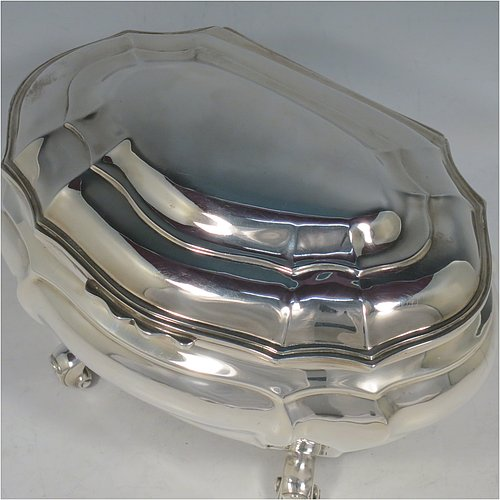 An Antique Edwardian Sterling Silver hand-chased Bonbonnier style heavy table box, having a shaped oval baluster body with a hinged domed lid and thumb-piece, and sitting on four cast scroll feet. Made by David Munsey of London in 1902. The dimensions of this fine hand-made antique silver box are length 20 cms (8 inches), width 14 cms (5.5 inches), height 12.5 cms (5 inches), and it weighs approx. 806g (26 troy ounces).