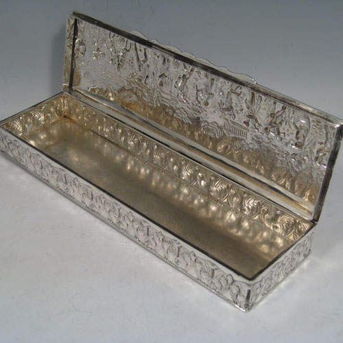 Antique Edwardian sterling silver hand-chased table box, having a rectangular body with a hinged lid, the lid being hand-chased with a Greco-Roman frieze, and the sides being hand-chased with anthemion-leaf decoration, and sitting on a flat base. Made by Nathan and Hayes of Chester in 1906. The dimensions of this fine hand-made silver box are length 28 cms (11 inches), width 8 cms (3.25 inches), height 3.5 cms (1.3 inches), and it weighs approx. 466g (15 troy ounces).