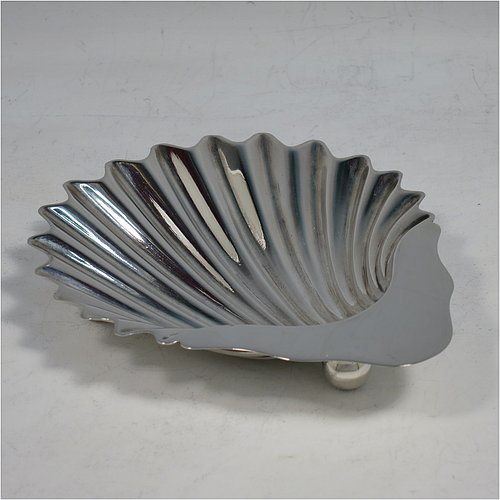 An Antique Victorian Sterling Silver butter shell, having a hand-chased scalloped body, and sitting on three ball feet. Made by William Gibson & John Langman of Sheffield in 1896. The dimensions of this fine hand-made antique silver butter dish are length 12.5 cms (5 inches), width 10 cms (4 inches), and it weighs approx 60g (2 troy ounces).