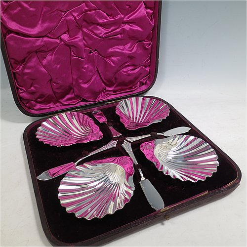 An Antique Victorian Sterling Silver set of four butter shells, having traditional scallop shapes, and sitting on three cast shell feet, together with four original butter knives in the Albany pattern, and all sitting in an original purple satin and velvet-lined presentation box. All made by Frances Higgins of London in 1884. The dimensions of this fine hand-made set of antique silver butter shells are length 12 cms (4.75 inches), width 10 cms (4 inches), with a total weight of approx. 385g (12.4 troy ounces).