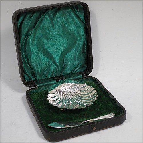 A very handsome Antique Victorian Sterling Silver butter shell and original butter knife, the shell having a hand-chased scalloped body, and sitting on three ball feet, the butter knife in the Old English Shell pattern, and all in their original green satin and velvet-lined presentation box. Made by John & William Deakin of Sheffield in 1898. The dimensions of this fine hand-made antique silver butter dish and knife are length of dish 10 cms (4 inches), width 8.5 cms (3.25 inches), length of knife 10.5 cms (4.25 inches), and they weigh a total of approx 51g (1.6 troy ounces).