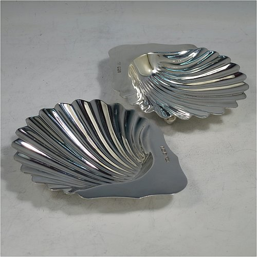 An Antique Victorian Sterling Silver pair of butter shells, having hand-chased scalloped bodies, plain shaped thumb-pieces, and both sitting on three ball feet. All made by Mappin & Webb of Sheffield in 1901. The dimensions of these fine hand-made antique silver butter dishes are length 12 cms (4.75 inches), width 9.5 cms (3.75 inches), height 2 cms (0.75 inches), and they have a total weight of approx. 146g (4.7 troy ounces).
