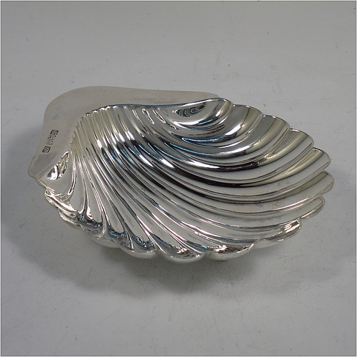 A very pretty Antique Edwardian Sterling Silver butter shell dish, having a hand-chased scalloped body, and sitting on three cast conch-shell feet. Made by Henry Atkins of Sheffield in 1904. The dimensions of this fine hand-made antique silver butter dish shell are length 12 cms (4.75 inches), width 10 cms (4 inches), and it weighs approx 60g (2 troy ounces).