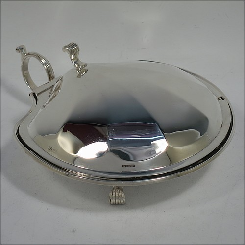 A very handsome and unusual Sterling Silver covered butter shell dish, having a hand-chased scalloped body, a hinged cover with a cast thumb-piece and knife slot, with a ring side-handle, a frosted cut removable liner, and all sitting on three cast reeded feet. Made by Henry Matthews of Birmingham in 1922. The dimensions of this fine hand-made silver butter dish shell are length 16.5 cms (6.5 inches), width 14 cms (5.5 inches), and it weighs approx 179g (5.7 troy ounces).
